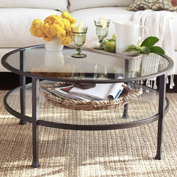 TANNER ROUND COFFEE TABLE - Our glass-topped coffee table keeps a room open and light. Its round shape works especially well with an L-shaped sectional, and it's also a great fit in smaller spaces. Its top and shelf provide plenty of room for a variety of uses.