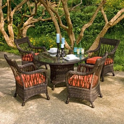 Woodard Serengeti All Weather Wicker Dining Set - Seats up to 6 - We know entertaining can be a lot of work - invitations have to be made, menus have to be planned, the house has to be cleaned, and the table has to be set. But we promise the Woodard Serengeti All Weather Wicker Dining Set - Seats up to 6 makes the whole process a little easier - and it's already easy on the eyes. This pretty, practical set comes in several configurations to best suit your entertaining needs, but all come with the natural, rustic style that's the hallmark of the collection.Every piece starts with durable, all-weather resin wicker, hand-woven over a sturdy aluminum frame built to withstand every gathering. Choose either an oval table, which seats up to six, or a round table, which seats up to four. Each table boasts tightly woven wicker along the tabletop sides and base, which is lightly shaped and footed with four short legs. Each is also topped with a clear glass piece that eliminates worry about spills - just wipe it with a clean, soft cloth.Two types of chairs are available: dining arm chairs and swivel rockers. Each features wicker thickly woven at the top of the back, along the softly curved arms, and around the lower apron. Branch-like open weave along the sides and back of every chair lighten the look. Swivel rockers move smoothly around the wide wicker base, which adds additional sturdiness so you can take in any angle without moving the entire chair with you. Color enters the picture in the form of a simple square cushion on every chair, available in a range of organic shades and all made of super-practical Sunbrella fabric that boasts a five-year warranty against fading.Each wicker piece is maintenance-free - hose off the wicker each season to keep it fresh. Everything is shipped fully assembled, too, for immediate use and includes a three-year limited warranty. Choose the oval table with four dining arm chairs and two swivel rockers; the round table with four dining arm chairs; or the round table with four swivel rockers.DimensionsRound table: 54L x 54W x 29H inchesOval table: 80L x 47W x 29H inchesDining arm chair and swivel rocker: 29L x 27W x 38H inchesAbout Sunbrella FabricSunbrella fabric is breathable and water-repellent. If kept dry, it will not support the growth of mildew as natural fiber will. It's easy to clean, requiring simple dusting off and soap and water. Beautiful and durable, Sunbrella fabric is a name you can trust in your outdoor furniture. Sunbrella fabric comes with a 5-year warranty against fading.All-weather Resin WickerSome of the most beautiful furniture is crafted using man-made resin wicker. Resin wicker is a synthetic plastic colored all the way through and stretched over a metal wire core. The resin is made with UV inhibitors to protect the resin from fading in sunlight. Resin products don't chip, break or get brittle with UV exposure. It's a beautiful, long-lasting choice in furniture that's easy to care for, requiring an occasional dusting and wipe-down with a damp cloth.Important NoticeThis item is custom-made to order, which means production begins immediately upon receipt of each order. Because of this, cancellations must be made via telephone to 1-800-351-5699 within 24 hours of order placement. Emails are not currently acceptable forms of cancellation. Thank you for your consideration in this matter.Woodard: Hand-crafted to Withstand the Test of TimeFor over 140 years, Woodard craftsmen have designed and manufactured products loyal to the timeless art of quality furniture construction. Using the age-old art of hand-forming and the latest in high-tech manufacturing, Woodard remains committed to creating products that will provide years of enjoyment.Most Woodard furniture is assembled by experienced professionals before being shipped. That means you can enjoy your furniture immediately and with confidence.Together, these elements set Woodard furniture apart from all others. When you purchase Woodard, you purchase a history of quality and excellence, and furniture that will last well into the future.Read more about the Woodard Guarantee by clicking the link on the product page.