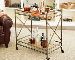 "New Products! - With our Kimber Bar Cart, you can take the party to the party. Clear, tempered glass shelves on top and bottom provide plenty of space for glassware and bottles. The simple elegant frame has ""X"" details that add a dash of architectural style and strength. When mobile, gallery prevents glassware and items from shifting off glass shelves. Comes fully assembled."