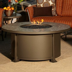 O.W. Lee Casual Fireside Cypress 54 in. Round Fire Pit Table - The O.W. Lee Casual Fireside Cypress 54 in. Round Fire Pit Table is a hassle-free way to go outdoors and enjoy the warmth of a fire. It's so hassle-free in fact that we wonder if we used to roast marshmallows and cook hot dogs over a campfire to justify the trouble of building the fire in the first place. You won't need to justify a thing with this convenient outdoor fire pit but you will need to pick the frame finish and table-top style that most appeals to your outdoor sensibilities. A standard propane tank powers the burner and is nestled safely inside the frame of rugged wrought iron. Inside the fire bowl you can choose from lava rock ceramic logs pebbles or fireproof glass beads to give it a look that's either traditional of modern. Runs on propane and/or natural gas conversion kit for natural gas is included. Materials and construction:Only the highest quality materials are used in the production of O.W. Lee Company's furniture. Carbon steel galvanized steel and 6061 alloy aluminum is meticulously chosen for superior strength as well as rust and corrosion resistance. All materials are individually measured and precision cut to ensure a smooth and accurate fit. Steel and aluminum pieces are bent into perfect shapes then hand-forged with a hammer and anvil a process unchanged since blacksmiths in the middle ages. For the optimum strength of each piece a full-circumference weld is applied wherever metal components intersect. This type of weld works to eliminate the possibility of moisture making its way into tube interiors or in a crevasse. The full-circumference weld guards against rust and corrosion. Finally all welds are ground and sanded to create a seamless transition from one component to another. Each frame is blasted with tiny steel particles to remove dirt and oil from the manufacturing process which is then followed by a 5-step wash and chemical treatment resulting in the best possible surface for the final finish. A hand-applied zinc-rich epoxy primer is used to create a protective undercoat against oxidation. This prohibits rust from spreading and helps protect the final finish. Finally a durable polyurethane top coating is hand-applied and oven-cured to ensure a long lasting finish. About O.W. Lee CompanyAn American family tradition O.W. Lee Company has been dedicated to the design and production of fine handcrafted casual furniture for over 60 years. From their manufacturing facility in Ontario California the O.W. Lee artisans combine centuries-old techniques with state-of-the-art equipment to produce beautiful casual furniture. What started in 1947 as a wrought-iron gate manufacturer for the luxurious estates of Southern California has evolved three generations later into a well-known and reputable manufacturer in the ever-growing casual furniture industry.