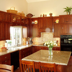 Face Frame Style Custom Kitchen Cabinets - This beautiful cherry kitchen features many doors cut for glass.  The owner wanted to display items only at the top of the cabinets, so we had the doors cut for glass only at the top. They have another area   With custom cabinets your choices ae endless.  This kitchen has all the comfort and convenience features anyone would want in their kitchen.  We made roll outs to fit certain items and configured the cabinets to house their TV.  Visit our web site to see photos of this fantastic kitchen and many many more!