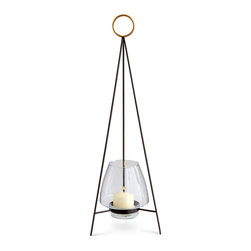 Tripod Ring Candleholder - Reminiscent of the candleholders found in Verona, Italy, the Tripod Ring Candleholder boasts a distinctive silhouette that positions the candle at the nadir of the triangular form. Three graphite rods are topped with a glimmering gold ring that lends old-world allure and allows for ease in carrying.