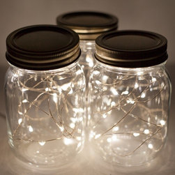 Mason Jar Fairy Lights - Battery-operated LED fairy lights in mason jars are an easy way to illuminate outdoor tables with little work involved. Just stuff the lights in a jar, and you're done. Because they're LEDs, the lights stay cool to the touch and last longer, requiring fewer AA battery changes.