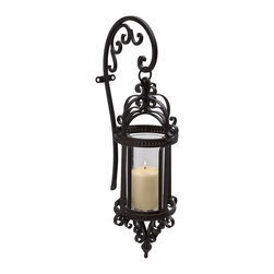 Imax - iMax Dempsy Hanging Wall Lantern X-87601 - This IMAX Dempsy Hanging Wall Lantern is a piece that certainly does not lack in details. It has a stunning wrought iron frame full of curvaceous scrolls that holds a simple glass shade. It's a dramatic and eye-catching piece with a distinctive look, and one that's sure to light up your home in style with the use of just one pillar candle.