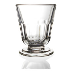 Perigord Tumbler - Placed on the table for all diners or offered around while lounging in the living room, the Perigord Tumbler advertises a worldly interest in practical glassware with a sleek, familiar transitional look.  Slightly faceted and beveled for an impression of substance, the tumbler from this collection of designer clear drinking glasses has a round foot for a hint of elite, urbane elegance.