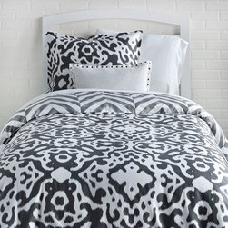 Urban Ikat / Tiled Chevron Reversible Duvet Cover and Sham Set - Urban ready. Switch up your style with this effortlessly chic reversible duvet cover and sham set. A  vivid charcoal color is printed on a crisp white cotton to form this beautiful large-scale, simple interpretation of the traditionally ethnic ikat print on one side of the duvet. On the reverse, a tiled chevron pattern in a distressed texture gives off a cool architectural vibe. he rich grey color works as a blank slate allowing you to pair any accessories to complete the look, also making this duvet set very long lasting. Made from 100% cotton sateen, this soft,  grey chevron duvet cover and sham set  is perfect for a classic gal with a little bit of edge.