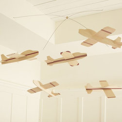 Balsa Wood Hanging Planes - Our own hearts are soaring over this balsa wood plane mobile. Subtle in color, this lightweight wooden set nods at classic childhood toys, and offers your little pilot something delightful to rest their eyes on from within the safety of their own crib.