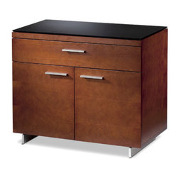 """BDI USA - Sequel Storage Cabinet - Features: -Available in Natural Stained Cherry, Espresso Stained Oak, Natural Walnut finishes. -Engineered to last a lifetime, all Sequel components are constructed of satin-finished, nickel-plated heavy gauge steel and richly finished wood panels. -Ideal for storing supplies and projects. -Offers a deep, full extension top drawer for easy access to contents. -Lower divided compartment includes two independently adjustable lower shelves allowing customization as needed. -The lower doors concel adjustable lower shelves, perfect for keeping projects and supplies organized and out of view. -Dimensions: 29"""" H x 35"""" W x 18"""" D. Sequel Office Suite Overview and Options: Sequel Configurations: The beauty of the Sequel collection is the virtually endless number of ways that it can be configured. Whether it's a small home office or a complete dedicated work space, Sequel allows to you create the office that is perfect for your needs. Check out our photo gallery for just a few examples of the offices that can be created with Sequel Office. Sequel Work Surface Options: The Sequel Desk is the cornerstone of the Sequel collection and is thoroughly engineered with easy access panels, integrated wire management, a unique multifunction system drawer and a luxurious micro-etched glass work surface. For smaller spaces, the Compact Desk is a versatile solution, also full of innovative features. The Sequel Return coordinates perfectly with the desks, or is a great laptop station on its own. Other components such as the Sequel Bridge, Peninsula and Corner Desk beautifully extend the work space by connecting directly to BDI's Storage Cabinets. Sequel Mobile Components and Cabinets: To keep files and office supplies organized, add Sequel's Mobile Components and Cabinets and gain versatile storage options for the small and large office space. Compact storage cabinets rest on locking casters and include file and supply drawers to keep folders and a computer"""