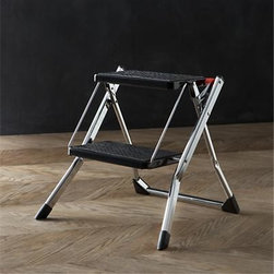 """Polder® Chrome Mini Step Stool - Life meets style™ at the intersection of form and function courtesy of the bright minds at Polder® Housewares. When it's just out of reach, reach for this compact, shorter step stool crafted of chrome-plated steel. Though conveniently lightweight, it's engineered for sure footing with a spring-loaded safety lock that secures the generous 12""""x8"""" nonskid steps. Folds to a slim 1"""" profile with carrying handles for convenient and space-saving storage."""