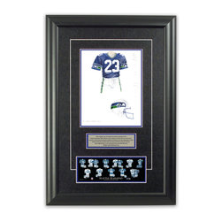"""Heritage Sports Art - Original art of the NFL 1983 Seattle Seahawks uniform - This beautifully framed piece features an original piece of watercolor artwork glass-framed in an attractive two inch wide black resin frame with a double mat. The outer dimensions of the framed piece are approximately 17"""" wide x 24.5"""" high, although the exact size will vary according to the size of the original piece of art. At the core of the framed piece is the actual piece of original artwork as painted by the artist on textured 100% rag, water-marked watercolor paper. In many cases the original artwork has handwritten notes in pencil from the artist. Simply put, this is beautiful, one-of-a-kind artwork. The outer mat is a rich textured black acid-free mat with a decorative inset white v-groove, while the inner mat is a complimentary colored acid-free mat reflecting one of the team's primary colors. The image of this framed piece shows the mat color that we use (Medium Blue). Beneath the artwork is a silver plate with black text describing the original artwork. The text for this piece will read: This original, one-of-a-kind watercolor painting of the 1983 Seattle Seahawks uniform is the original artwork that was used in the creation of this Seattle Seahawks uniform evolution print and tens of thousands of other Seattle Seahawks products that have been sold across North America. This original piece of art was painted by artist Bill Band for Maple Leaf Productions Ltd. Beneath the silver plate is a 3"""" x 9"""" reproduction of a well known, best-selling print that celebrates the history of the team. The print beautifully illustrates the chronological evolution of the team's uniform and shows you how the original art was used in the creation of this print. If you look closely, you will see that the print features the actual artwork being offered for sale. The piece is framed with an extremely high quality framing glass. We have used this glass style for many years with excellent results. We pa"""