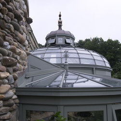 Greenhouse - The central area is covered by a dome glass roof with a lantern topped by a specially commissioned glazed rooster finial  made in France, which compliment other similar finials on the main house.Hampton Conservatories, LLC