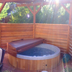 Hot tub installations - A private retreat is created by adding a small fenced area and arbor cover.