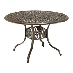 HomeStyles - Floral Blossom Taupe 48 Inch Dining Table - Assembly Required. Hand-applied gold specking sealed with a clear coat. 2-inch umbrella hole. Nylon glides on legs for stability. Stainless steel hardware. Dimensions: 48 in. W X  48 in. D X  29 in. HBy combining outdoor elements such as ceremonial and abstract floral designs, the Floral Blossom 48-Inch Round Dining Table by Home Style is brought to life. Table is constructed of cast aluminum in a powder coated taupe finish with hand applied gold specking, sealed with a clear top coat. Other features include attractive patterned table top that has 2-inch umbrella hole with black cap, and nylon glides on legs for stability.  Elegant design and sturdy construction, this piece is finished with stainless steel hardware.  Assembly required.  Size: 48w 48d 29h