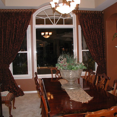 """Draperies - Stationary drapery side panels tied back and puddled. Installed on 2"""" wood poles and rings."""