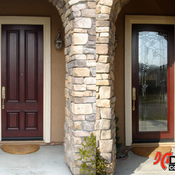 "Before & After - Wrought Iron Insert - This handcrafted beveled glass panel represents our ""Tuscan"" design, fabricated by fine craftsmen and insulated between two layers of tempered clear glass. To install our designs into your existing door we use stylish raised hardwood frames that we stain to match the finish of your door so that it looks as if it has always been a part of your door, not something that has been retrofitted."