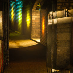 """In the Cellar, 16x20"""" fine art color photograph - Barrels and bottles backlit with colored lights in a wine cellar. Available as a 16x20"""" limited edition fine art photograph, printed archivally on photo rag paper. Unframed."""
