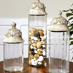 Acorn Canisters - Set of 3 - Heavily stylized acorns surrounded by flourishes of oak leaves � classically used in formal interiors and upper-class jewel boxes to symbolize the immortality of the spirit � are here made the crowning interest of the fluted glass Acorn Canisters. Atop each clear glass column, the domed and knobbed acorn lids are finished in a distressed neutral tan for a hint of age.
