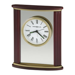 Howard Miller - Victor Tabletop Clock w Wood Frame and Brass - Striking, table top alarm clock is made of both wood and glass. Features contoured sides. The top, bottom and sides are wood and enjoy a satin Rosewood finish. For added interest, the polished brass clock face is designed to float between the glass panels. This handsome wood and glass alarm clock features contoured sides, with wood top and base in a satin Rosewood finish. Satin brass plates accent the top and base. The polished brass-tone bezel and dial are suspended in a glass panel. The white dial offers Roman numerals and black hour and minute hands with luminous inserts beneath a glass crystal. Felt bottom protects your desktop. Quartz, alarm movement includes the battery. 6 in. W x 2 in. D x 7 1/4 in. H