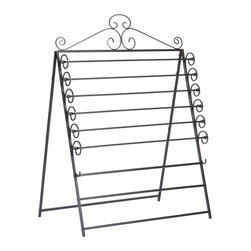 "Holly & Martin - Evelyn Easel/Wall Mount Craft Storage Rack in - 6 movable racks for standard size 30 in. wrapping paper. 2 fixed racks for tissue paper. Converts easily from an easel to a wall mount unit. Made from metal. Black finish. Standing dimension: 34.75 in. W x 27.5 in. D x 46.25 in. H (13 lbs.). Assembly InstructionsThe perfect solution for storing you wrapping paper and tissue paper this easel is a must have for any craft room. Featuring a beautiful scroll work design this easel can hold up to six standard 30"" rolls of wrapping paper and has two addition racks to hang tissue paper on. This easel also conveniently converts to a wall mount storage unit to fit your needs. Add one to your home today!"