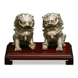 China Furniture and Arts - Hand Forged Silver Foo Dogs - Always standing in pairs, Foo Dogs are fantasy lions in Chinese mythology who serve as guardians to prevent harmful things from happening to the family. This handsome pair are standing in commanding posture. The male, with a paw on a symbolic ball, protects the world, while the female, with a paw on a cub, protects the dwelling. This handsome pair is hand forged silver by artisans in China with fine detail. Wooden stand sold seperately.