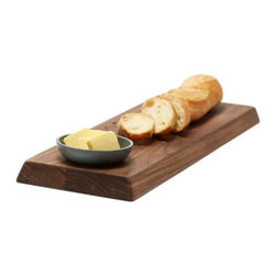 Teroforma - Bread and Butter Board by Teroforma - The Teroforma Bread and Butter Board doubles the functionality of a traditional bread board. Made out of Walnut, this board has one flat side ideal for cutting and a sloped side for crackers, pre-sliced bread and catching crumbs. The included soapstone bowl fits into a carved opening on either side to serve butter or other spreads. Based in Norwalk, Conneticut, Teroforma was founded in 2006 by Andrew & Anna Hillman to make the dining table a fun, friendly and fashionable meeting place. Renowned especially for their Whisky Stones, Teroforma also creates a wide range of modern kitchen tools, decorative porcelain, dinnerware, linens and so forth to make gatherings around the table memorable ones.