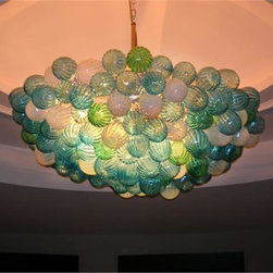 """Belle Meade Hot Glass - Gourd Chandelier - This captivating chandelier is shown in subdued hues of Aqua, Emerald Green, and Opal White. The individually hand blown glass pieces are all Gourd-shaped (see additional photo #3 for detail of a """" gourd"""" ). Smaller Gourds are placed behind the larger ones, which fills the voids and prevents any visibility of the inside of the chandelier. Note- This is a representational item that can be commissioned. These exquisite designs are very diverse and can be custom made to fit any project. Other colors, sizes, and shapes are available so please call for more details. Allow us to help turn your vision into a reality. Note- This chandelier is lit from within the armature by easily replaceable 75 watt halogen bayonet bulbs. The lighting system is made from UL listed parts. The armature is shaped appropriate to the chandelier. Note- These chandeliers are suspended by a thin, high strength cable, the length of which must be specified when ordering. The weight for these chandeliers averages 30 pounds per 50 pieces. Due to the many different styles and types available, a ceiling canopy is not provided but can easily be obtained through your electrician. Note- If this item will be viewed from above, such as in a stairwell, the top will need additional pieces covering the armature at additional cost. Please call us for a price quote and specify this when ordering.  LED and Compact Fluorescent lighting are both available. Call for details.  Please note that the price listed pertains to a fixture that will appear very similar to the light shown in the featured photograph and as outlined in the accompanying description.  Virtually all of our artisan crafted fixtures can be customized regarding size, shape, and / or color(s).  Please call for details."""