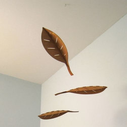 Schmitt Design - Mora Mobile by Schmitt Design - The Schmitt Design Mora Mobile floats in the air like falling leaves. Named after the Moraceae, or fig, family Mora features three large fig leaf-shaped elements made out of warm cherry wood veneer. The leaf halves are tabbed together along the spine, giving the pieces added dimension and orienting the wood grain to mimic natural leaf veins. In 2012, Schmitt Design became the new name for Adrift Mobiles, founded by Brian Schmitt. The name change came about as, while still specializing in contemporary mobiles for adults, the company has expanded to include a line of award-winning modern lighting, clocks and furniture. All Schmitt Design pieces are created and manufactured in Sacramento, California.