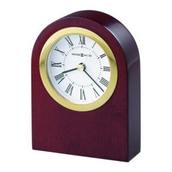 Howard Miller Rosebury Desktop Clock - Clean simple lines define the Howard Miller Rosebury Desk Clock finished in satin rosewood on select hardwoods. The white dial features a polished gold-tone bezel glass crystal black Roman numerals and black hands with a brass second hand. Full felt bottom protects your desktop. Quartz movement includes the battery.There's a certain level of expectation that comes with the Howard Miller name. And then there's the steady stream of surprises that make you stop in your tracks and take a second look. From traditional to hot trends and floor clocks to wine furniture you'll find even more than you expected at Howard Miller. Fine details expert craftsmanship and beautiful materials; no matter what your taste or budget a Howard Miller clock fits the bill.About Howard MillerBeginning in the 1920's Howard Miller clocks have impressed all who see them with superior quality and design. Howard Miller wall floor and mantel clocks are crafted to last for generations and to perfectly accent your home.The company's founder Howard C. Miller began manufacturing wall and mantel clocks in Michigan. Evolving to encompass cabinet making and other furniture design - all renowned for quality and style - the Howard Miller company proudly stands behind its reputation as the World's Largest Clock Manufacturer.