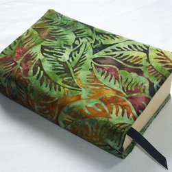 """Cloth Book Cover, Jungle Batik and Hand Dyed Fabric, Fits Most Mass Market Paper - Protect your book's cover and your privacy, all while making a fashion statement, with this beautiful fabric book cover! Made with a stunning batik that resembles jungle leaves in green, brown and burgendy, and lined in a coordinating grass green hand dyed cotton. A sewn-in ribbon bookmark is included and the light fleece batting gives it nice substance.Fits most mass market paperback books, measuring about 7"""" x 4-1/2"""", up to 650 pages."""