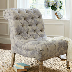 Lucia Slipper Chair - Lucia brings romance to the boudoir with its feminine lines, petite scale and delicate detailing. The faded blue toile upholstery is trimmed with traditional button tufting along the scrolled, angled seat back. Built atop a solid white American oak frame, it has antiqued brass casters on the turned front legs. The armless silhouette makes it a lovely choice for a vanity or grouped in pairs as a charming bedroom seating area.