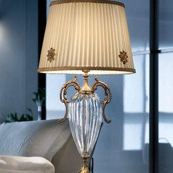 """6021/6026 TL1 P Table Lamp - The 6021/6026 TL1 P Table Lamp is part of a collection of High End light fixtures designed by Studio Stile Masiero in Italy for Masiero. This table lamp is a beautiful and harmonious piece that brings to classicism and modernism a new perspective. 6021/6026 TL1 P table lamp is an elegant light fixture consisting of a stand with an internal metal rod covered with transparent glass enriched with brass fusion decorations in burnished or polished gold finish. One delicate ivory Pongè lampshades that sits on top of the stand provides a diffused light. This is a stylish and contemporary table lamp that will light up any environment. Illumination is provided by E14 60W Incandescent bulb (not included).     .proddesc p{font-family: Verdana, sans-serif; font-size:8pt!important;}   .pdtable{font-family: Verdana, sans-serif; font-size:8pt!important;padding:10px;} Product Details: The 6021/6026 TL1 P Table Lamp is part of a collection of High End light fixtures designed by Studio Stile Masiero  in Italy for Masiero. This table lamp is a beautiful and harmonious piece that brings to classicism and modernism a new perspective. 6021/6026 TL1 P table lamp is an elegant light fixture   consisting of a stand with an internal metal rod covered with transparent glass enriched with brass fusion decorations in burnished or polished gold finish. One delicate    ivory Pongè lampshades that sits on top of the stand provides a diffused light.   This is a stylish and contemporary table lamp that will light up any environment. Illumination  is provided by  E14 60W Incandescent    bulb (not included). Details:                         Manufacturer:            Masiero                            Designer:            Studio Stile Masiero                            Made in:            Italy                            Dimensions:                        Height: 11.8""""(30cm) X Diameter: 6.3""""(16cm)                                         Light bulb:                        E14"""