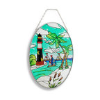Zeckos - Nautical Lighthouse, Sailboats and Beach Oval Glass Suncatcher 9 In. - This colorful sun catcher adds a nautical accent to any window, featuring 3 sailboats, a lighthouse, and a beach with 2 palm trees. The palm fronds and cattails have a crystallized texture, adding some depth to the piece. The sun catcher measures 9 inches tall, 7 inches wide, and has a 2 inch drop from the chrome chain hanger. It makes a great gift for friends and family that is sure to be admired.