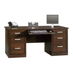Sauder - Sauder Office Port Executive Desk in Dark Alder - Sauder - Computer Desks - 408289 - Sure lots of office and home furnishing manufacturers can help you create an organized comfortable and fashionable place to live. But Sauder provides a special kind of furniture that is practical and affordable as well as attractive and enduring. As North America's leading producer of ready-to-assemble furniture we offer more than 500 items that have won national design awards and generated thousands of letters of gratitude from satisfied consumers.