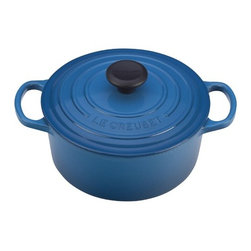 Le Creuset - Enameled Cast Iron 5 1/2-Qt. Round Dutch Oven - For generations, families have come to cherish this everyday French Oven (or Dutch oven, referred by most people). Ideal for simmering, marinating, poaching, braising, and browning; this piece moves from the stove or oven to the table and can store leftovers in the refrigerator or freezer! The tight fitting lid creates a blanket of heat, sealing in flavor and moisture, and is equipped with a phenolic knob which is oven safe up to 480 Degrees F. The Le Creuset enameled cast iron pieces evenly spreads heat and retains heat longer than other cookware materials. Features: -Dutch oven.-Material: Enameled Cast Iron.-Round shape.-Enhanced handles are 45% larger, distributes the weight evenly and easier to grip when wearing oven mitts.-Improved ergonomic knob, for easier grip, and now resistant up to 480 degrees.-Phenolic knob is oven safe to 480°F.-Lid traps heat and seals in flavor and moisture.-Works well on all heat sources, including induction and oven safe.-Ideal to use when making soups, rice dishes, casseroles, roasts, quiches, one pot meals, baked recipes, desserts, cakes and breads.-Refrigerator and freezer safe.-Dishwasher safe, but Hand washing is recommended.-Capacity: 5 1/2-Qt..-Made in France.-Provides even heat distribution and superior heat retention; colorful exterior enamel resists chipping and cracking.-Advanced sand-colored interior is durable, makes it easy to monitor food as it cooks to prevent burning or sticking.-Collection: Enameled Cast Iron.-Distressed: No.-Country of Manufacture: France.Dimensions: -Dimensions: 3.25'' H x 7.13'' W x 7.13'' D.-Overall Product Weight: 10.2 lbs.Warranty: -Lifetime limited warranty.