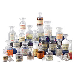 Vintage Apothecary Jars - Set of 24 - The details of the labels affixed to each tiny hand-blown bottle in this Set of Twenty-Four Vintage Apothecary Jars are worth hours of examination. Every one of the two dozen little vessels has a different label, as well as its own stopper, a slightly varied size, and minor imperfections resulting from handcrafted roots. Use as an artful display or as tiny bud vases.