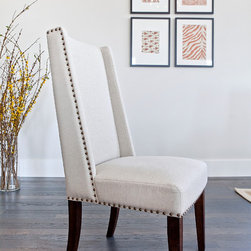 Tucker Dining Chair - French country-inspired with a contemporary twist, our Tucker Dining Chair is fully upholstered with a sand linen-blend fabric and finished with a bronze nailhead trim. We love the cocooning comfort of its slight wing shape and the sleek look of its dark stained wood legs.