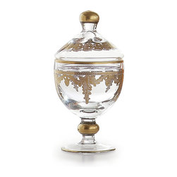 Baroque Gold Small Canister - A cultured decorative element in the bathroom or on the dresser which also provides an attractive place to tuck away necessities, the Baroque Canister is a small stemmed vase with a matching cover, both hand-crafted in Italy from crystal-clear glass, then lightly painted with smooth coats of 24-karat gold to cover the etchings of fabulous botanical draperies and to highlight the rims and globes of the flawlessly-produced glass pieces.