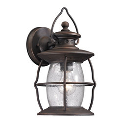 Elk Lighting - EL-47040/1 Village Lantern 1-Light Outdoor Sconce in Weathered Charcoal - Historic charm is captured in the Village Lantern Collection. This series has a clear glass fount inside a weathered charcoal finished wire frame. The handle that adorns the top of the fixture captures the authenticity reiminsant of the function these type of lights had years ago.