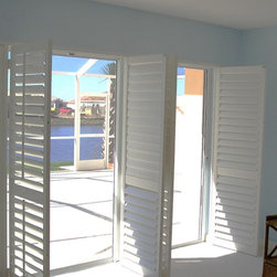 Window Treatments for Sliding Doors - Plantation shutters to mimic French doors.  Rather than use a traditional bypass on track plantation shutter or a bifold on track these shutters are mounted with T posts and open into the room.  Here they are shown in the open position.