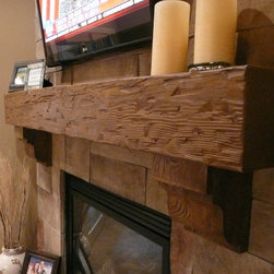 Fireplace Mantels - Tuscany faux wood mantel shelf with matching corbels adds a rustic touch to a sleek stone fireplace.