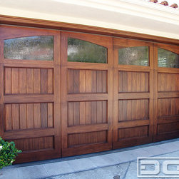 "Dynamic Garage Door - California Dream 13 | Custom Designed & Manufactured Carriage House Garage Door! - The jambs on this Custom Mahogany Garage Door were redone in a hand-routered Mahogany trim that frame this piece of art! Arched windows with antique glass inserts crown the top panel on this overhead custom garage door while the wooden trim found throughout the doors design wittily hides the section cuts. With its beautiful variant wood grains and colors topped off with antique glass window panes and frame-like jams, this garage door did not need anything else to make it a successful "" Œuvre d'art!"""