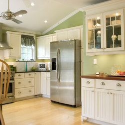 The Kitchen Loft - This kitchen renovation was done as part of a rehabilitation of the back of the home.  In addition, internal walls, which had chopped up the space, were removed creating a vibrant, open space.  The homeowners chose a country style door and combination painted finish from Embassy, a semi-custom product line of Omega Cabinets.