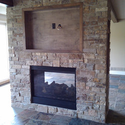 See through fireplace - A see through fireplace with Cavanal thin veneer natural stone exterior.  Stone provided by Sturgis Materials.