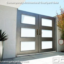 Dynamic Garage Door - A Steel & Frosted Glass Gate With Modern Chrome Locking Handle & Electric Strike - Contemporary architecture offers a variety of fine lined custom design options typically eclectic in taste in a variety of construction materials available today. This contemporary custom garage door follows a trendy style that incorporates natural wood, frosted glass and aluminum window framing that evokes a unique visual architectural statement. With Dynamic Garage Door's expertise in custom crafting garage doors, your imagination is the limit and making it a reality our challenge.