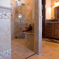 Mountain Rustic Zero-Entry Shower - This modern rustic bathroom has a door drain installed for a truly accessible zero-entry shower. The tile work is allowed to shine through, unbroken by the traditional drain that would normally be found in the center of the shower. If it is installed correctly and the output of water is less that the recommended output of the drain, there is no need to worry that water will run out of the shower across the threshold.