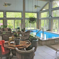 Endless Pools - Original Endless Pools®, Greenhouse - The crown jewel of this multi-purpose room: a partially in-ground Endless Pool. Its blue interior pops in the plentiful sunlight and against the room's taupe furnishings. LOVE the wine barrel swivel chairs too!