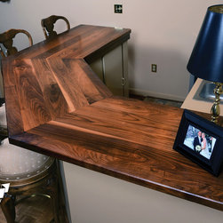 Walnut Neo-Angle Bartop - Maryland Wood Countertops a Division of OE Custom was hired to build a bar for a basement remodel. The plank construction walnut top with mitered edges creates a nice bartop with a finished furniture look, rather than a butcherblock appearance. Not only does the top contain sapwood to add to the contrast in colors of the walnut, but it also incorporates gentle and drastic wood grain patterns, randomly.