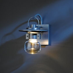 Hubbardton Forge - Mason Outdoor Wall Sconce by Hubbardton Forge - A sparkling jewel for outdoor spaces. The Hubbardton Forge Mason Outdoor Wall Sconce features a hook-hung lantern silhouette, made new and modern with a tiered, circular aluminum cap. A metal cuff around the top of the thick blown-glass shade conceals the light source, creating an ethereal effect like fireflies caught in a jar. A charming choice for flanking entrances, alongside garden paths and more. Hubbardton Forge, headquartered in Hubbardton, Vermont, hand-forges simple and elegant metal lighting fixtures and accessories, combining ancient hand-forging techniques with environmentally-sound finishing practices.