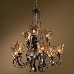 Uttermost - Vetraio 2-Tier Chandelier by Uttermost - The Uttermost Vetraio 2-Tier Chandelier was designed by Carolyn Kinder with layer upon luscious layer of hand-made Toffee Art glass radiating a warm, golden glow throughout any Old World style dining room or entryway. The nine glass shades are held up and complemented by a curvaceous iron frame, finished in a deep Oil Rubbed Bronze.Since 1975, Uttermost has made it their mission to make great home accessories at a reasonable price. From their headquarters in Rocky Mount, Virginia, Uttermost continues to meet this goal with sophistication and grace through their current line of quality, designer-driven lighting, home furnishings and accessories.The Uttermost Vetraio 2-Tier Chandelier is available with the following:Details:9 hand-made Toffee Art glass shadesIron frameOil Rubbed Bronze finishCeiling canopy7' chainDesigned by Carolyn KinderLighting:Nine 60 Watt 120 Volt Candelabra Base Incandescent lamps (not included).Shipping:This item usually ships within five business days.
