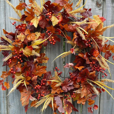 """Fall Wreath - This beautiful wreath is characterized by life-like leaves in various stages of fall color. Beautiful berries, heads of wheat, and pine cones peek out from the leaves. This wreath is a perfect harvest time decoration! This wreath was made on a grapevine base measuring about 18""""."""